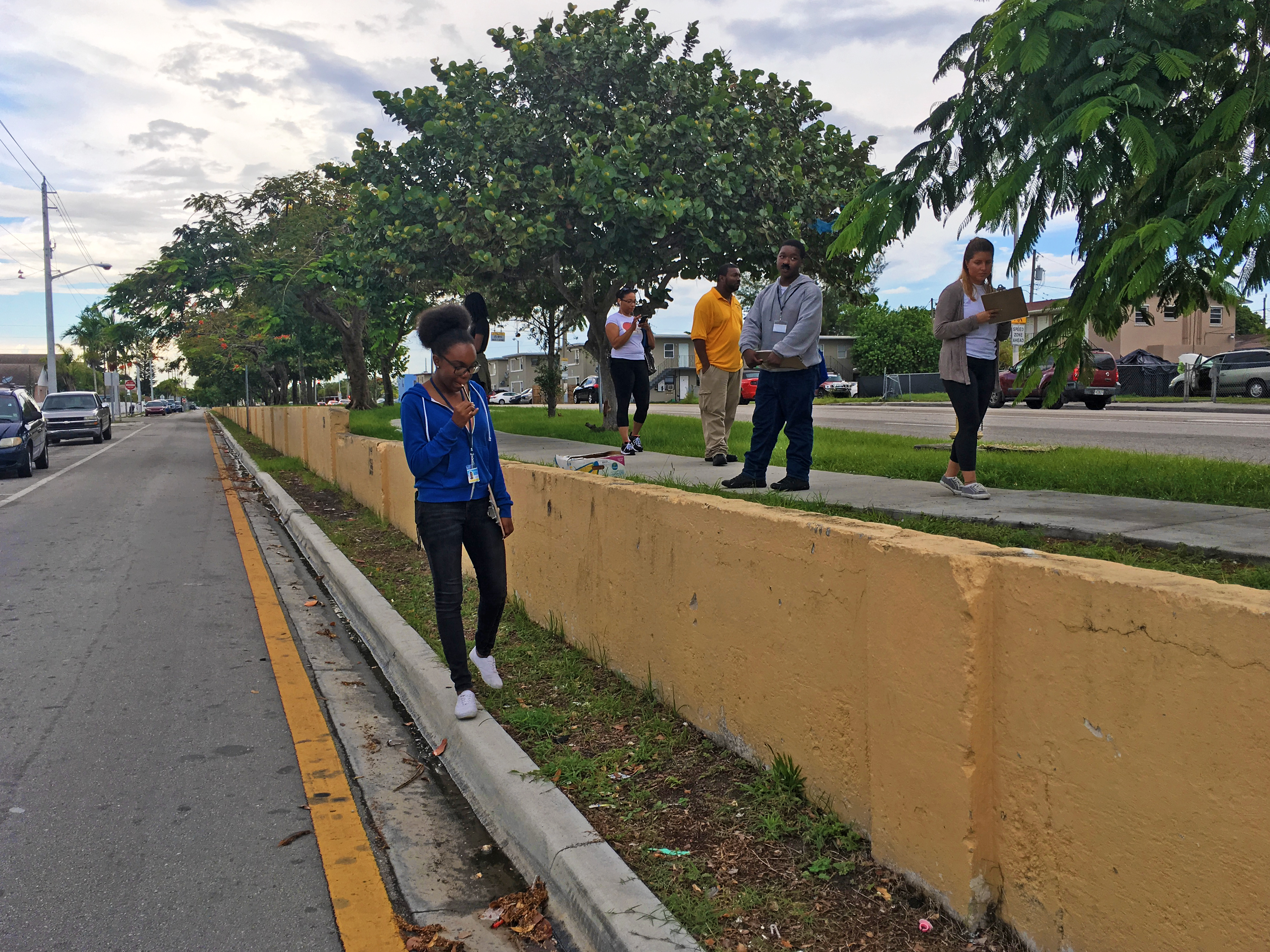 Teenagers walking along remains of race wall in Liberty City, Florida