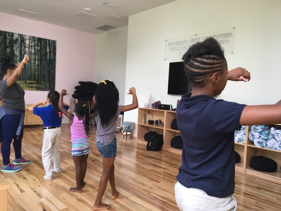 Young children learning dance poses with Teaching Artist