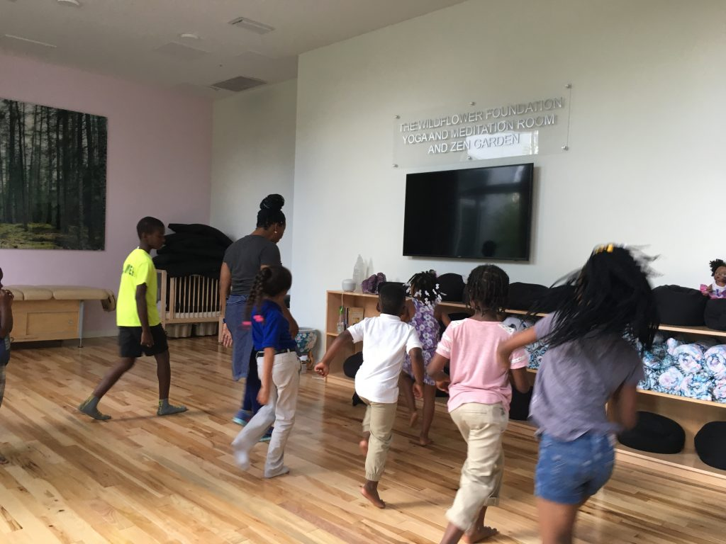Young boys and girls learning dance steps from teaching artist.