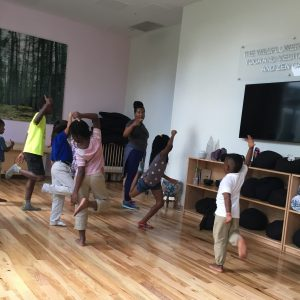 Young boys and girls actively learning choreography with teaching artist.