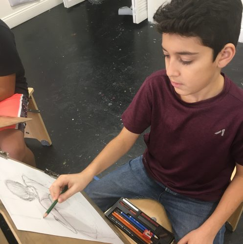Middle school boy drawing with pencil on paper.
