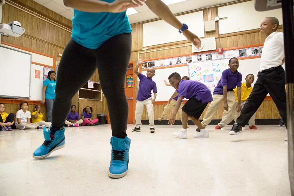 group of students learning choreography with teaching artist